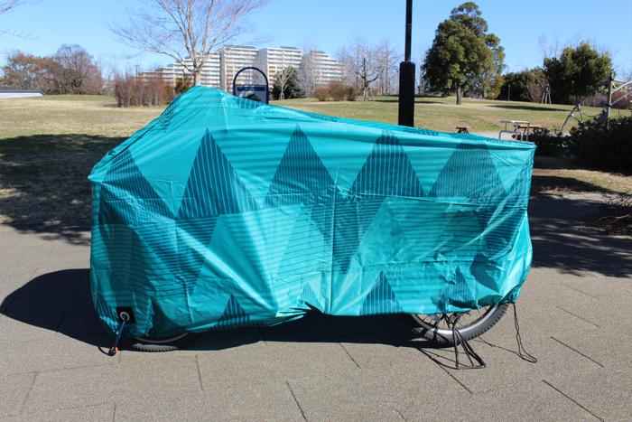 「サイクルカバー Triangle」価格:1,580円/自転車全体を覆い粉塵などから自転車を守るカバー。裾絞りできるのでぴったりフィット、下部の面ファスナーでバタつき防止、鍵穴付きで盗難防止にも。爽やかなカラーで派手過ぎず、玄関前などに置いても圧迫感のない使いやすいデザインです。