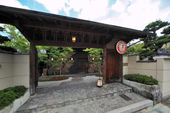 重厚な門構えからは、木村英輝氏の手がけた壁画がのぞく(eXcafe京都嵐山本店)
